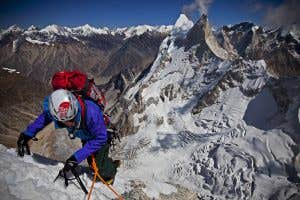 Conrad Anker climbing out fully geared up with helmet and hiking backpack.