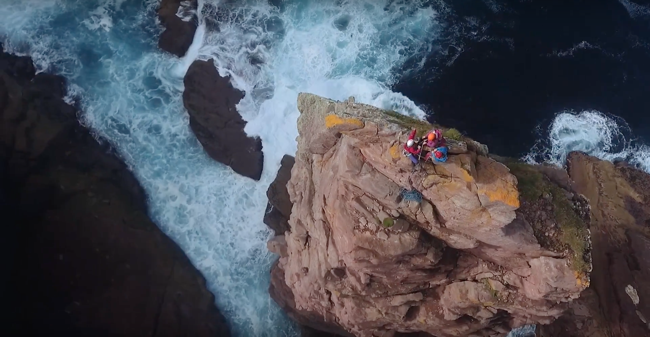 Climbers on top of a tall cliff over smashing waters