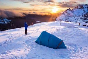 Hiker infront of tent looking out into the sunset over a valley in the snow.