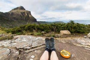 Hikers legs and boots next to his dinner of curry and couscous for dinner at Shelf Camp looking out over the Tasmanian wilderness.