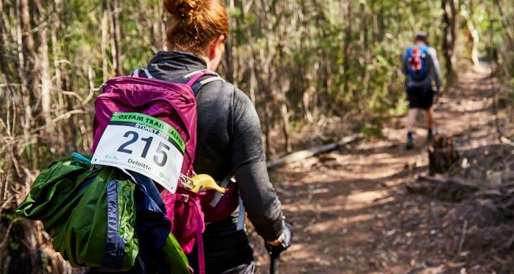 Image of a woman walking the Oxfam Trailwalker 100km, in a bushy section.