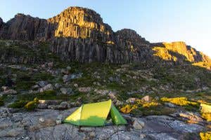 Tent pegged down with rocks at shelf camp in Tasmania