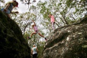 Adventurous girls leaping between boulders.