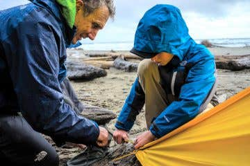 Father and son putting up a tent together on a beach and wearing The North Face jackets