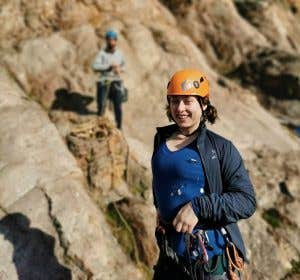 Evie, an adventurous Melbourne team member out rock climbing with her climbing gear and helmet on.