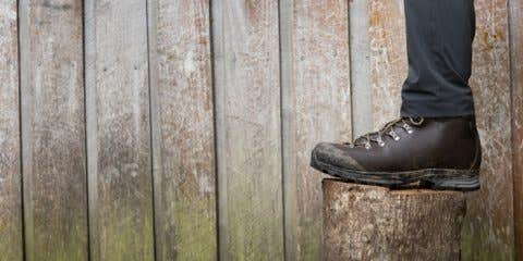 Scarpa Boot being worn in front of a wooden hut.