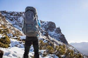 Hiker wearing an Osprey pack in snow covered mountains