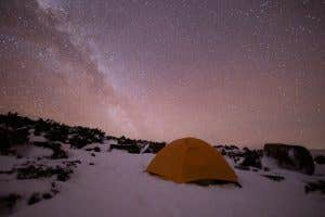 Hiking tent in the snow under a starry night