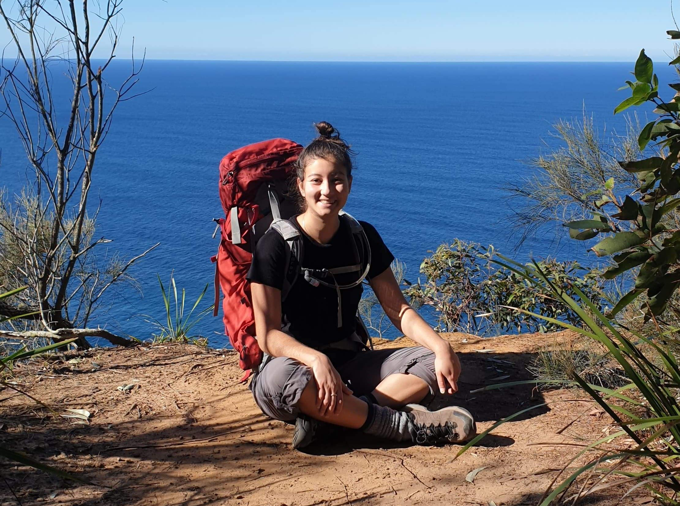 Paddy pallin Team Member Ranuka at home on the trail sitting on a cliff next to the ocean while wearing an osprey pack