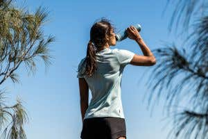 Trail runner enjoying a refreshing drink form a CamelBak Podium Bottle