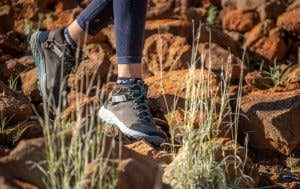Image of woman walking along uneven rocky surface with Teva Grandview.