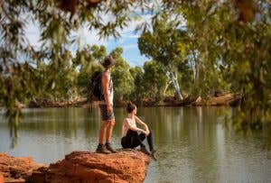 A standing man and a seated woman looking out over a river from a rocky outcrop.