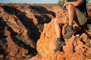 Man sits with Teva Arrowood Boot overlooking a gorge.
